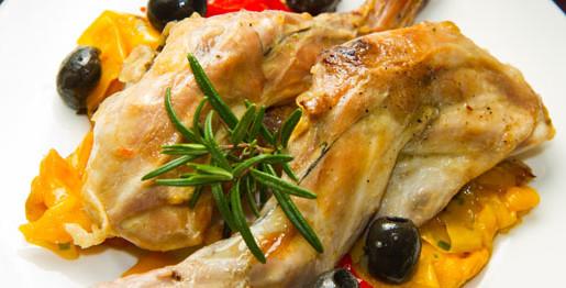Coniglio con peperoni, olive nere e rosmarino